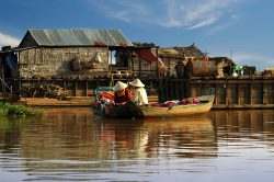 Local boat on the Tonle Sap lake surrounded by floating and stilted villages