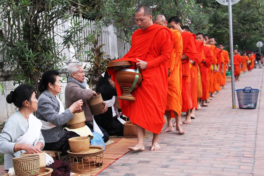 Saffron robed monks at Almsgiving Ceremony - Luang Prabang city - Places to visit in Laos